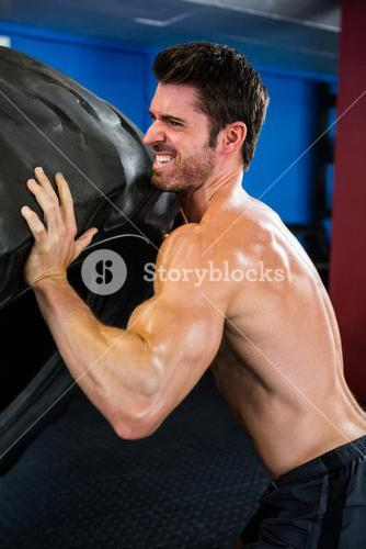 Shirtless male athlete lifting tire