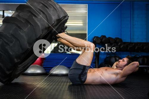 Man exercising with tire in gym