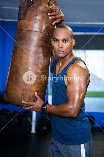 Confident male athlete by punching bag