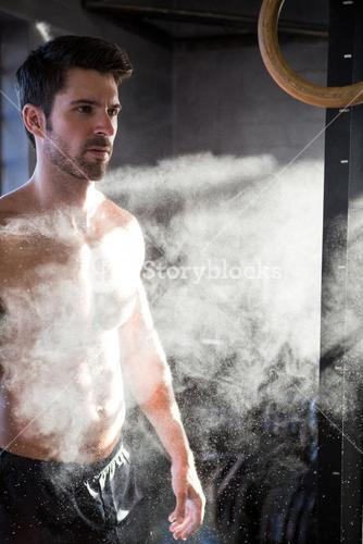 Male athlete standing by chalk dust