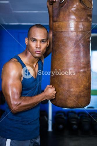 Determined young man standing by punching bag