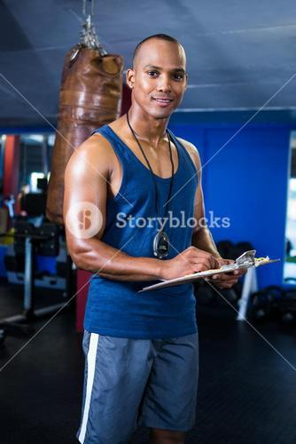 Male trainer with clipboard in gym