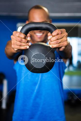 Man covering face with kettlebell in gym