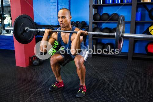 Male athlete weightlifting in fitness studio