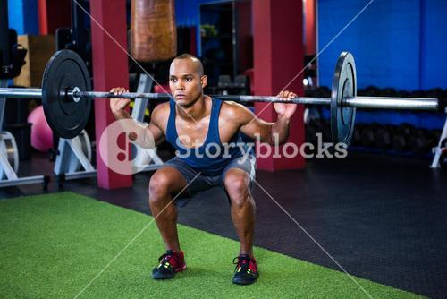 Young man weightlifting in fitness studio