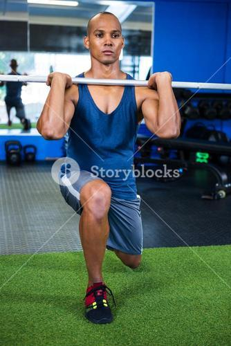Man lifting barbell in fitness studio