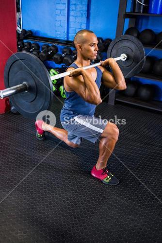 Determined man lifting barbell in fitness studio