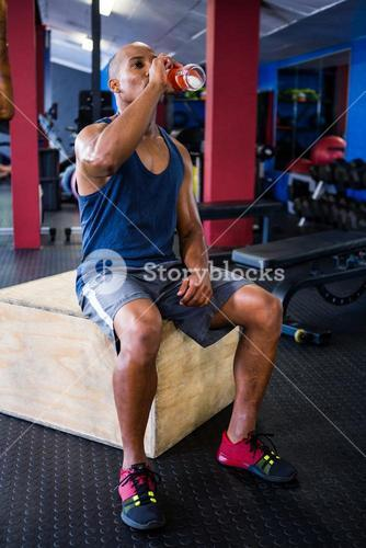 Male athlete drinking juice in gym