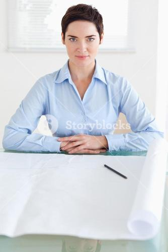 Serious shorthaired businesswoman with a architectural plan