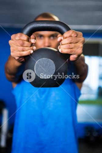 Man covering face with kettlebell