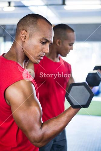 Man exercising with dumbbells against mirror