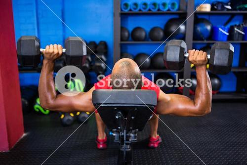 Man with dumbbells on weight bench