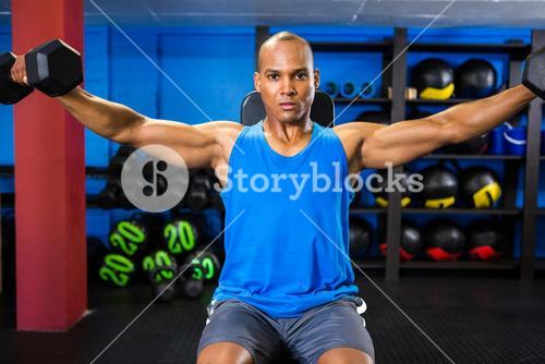 Determined male athlete exercising with dumbbells