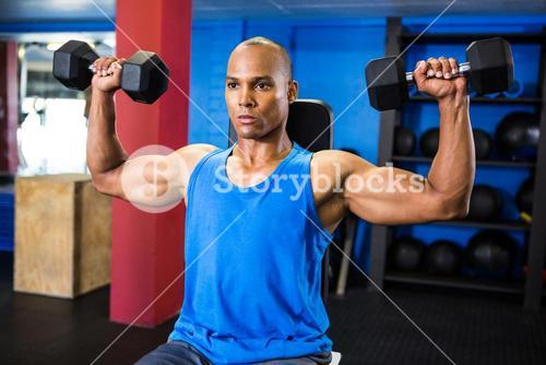 Determined athlete exercising with dumbbells