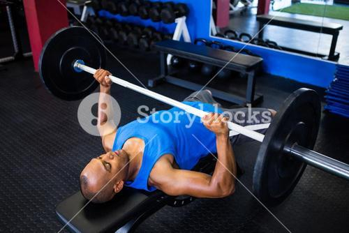 Male athlete doing bench press in fitness studio