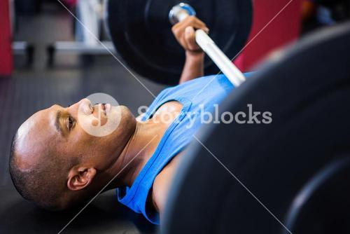 Determined male athlete exercising with barbell