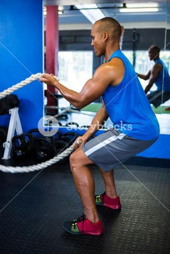 Male athlete exercising with ropes in gym