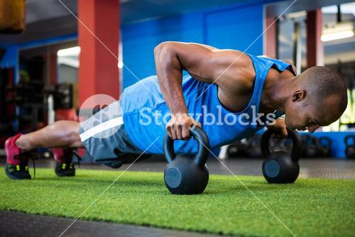 Athlete doing push-ups with kettlebells