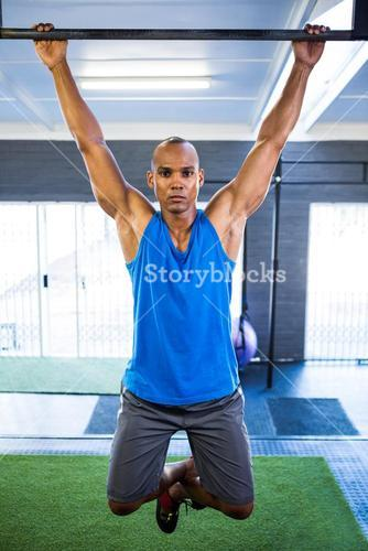 Male athlete doing chin-ups in gym