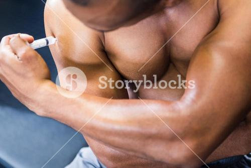 Muscular man injecting steroid
