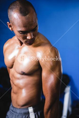 Muscular man looking at arm in gym