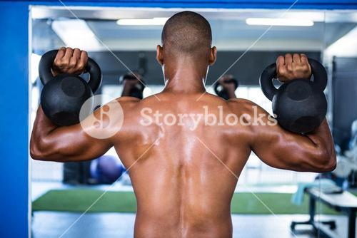 Man exercising with kettlebells in gym
