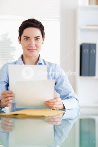 Portrait of a Businesswoman sitting behind a desk with papers