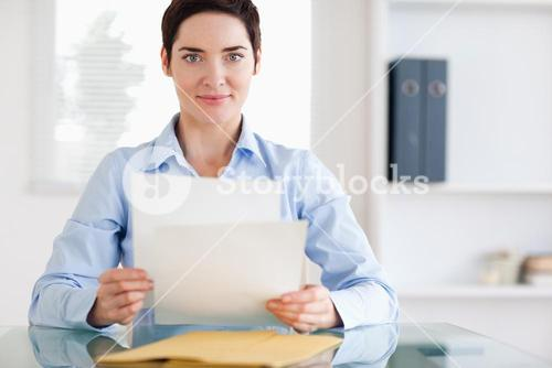 Portrait of a brunette Businesswoman sitting behind a desk with papers