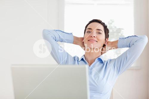 Shorthaired relaxed businesswoman with a laptop looking into the camera