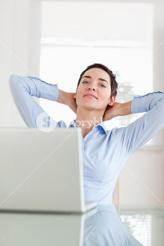 Relaxed businesswoman with a laptop looking into the camera