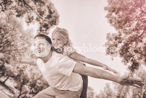 Father giving daughter a piggy back in park