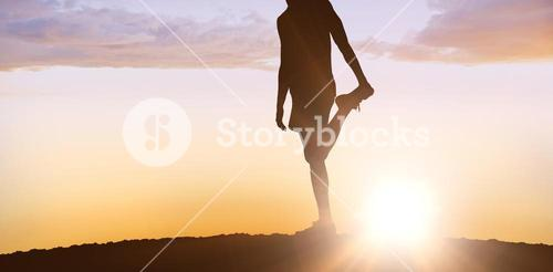 Composite image of sporty man stretching his leg