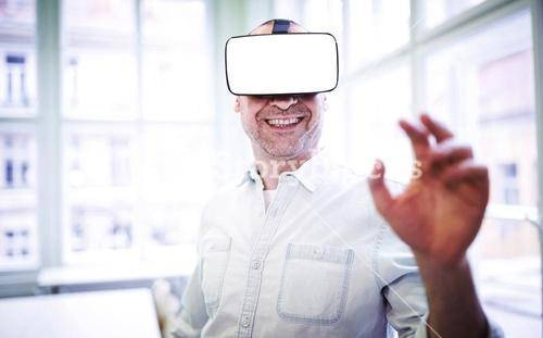 Smiling graphic designer using virtual reality headset