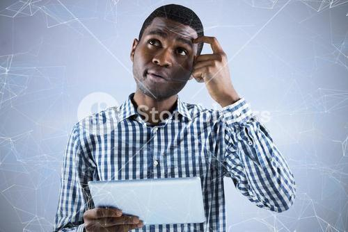 Composite image of young businessman thinking and holding tablet