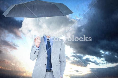 Composite image of smiling businessman looking at camera under umbrella