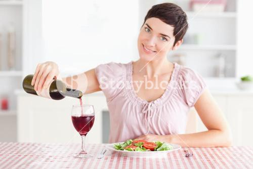 Woman pouring redwine in a glass
