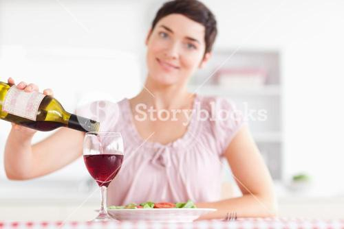 Smiling Woman pouring redwine in a glass