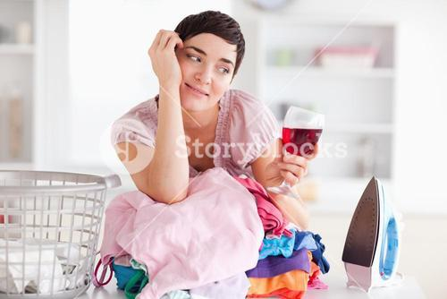 Cute Woman with wine and a pile of clothes
