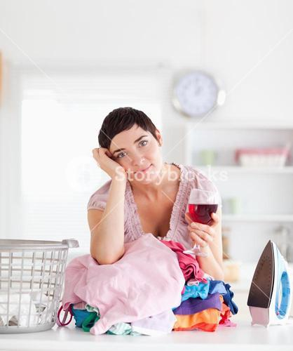 Brunette Woman with wine and a pile of clothes