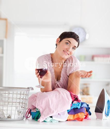 Smiling Woman with wine and a pile of clothes