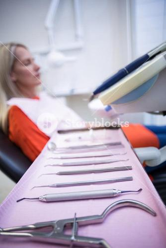 Woman relaxing on dentist chair with dental tools on foreground