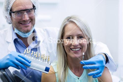 Dentist holding teeth shades while female patient smiling