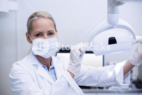 Female dentist holding dental lights