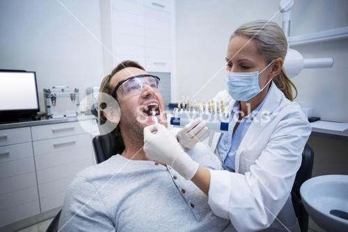 Female dentist examining male patient with teeth shades