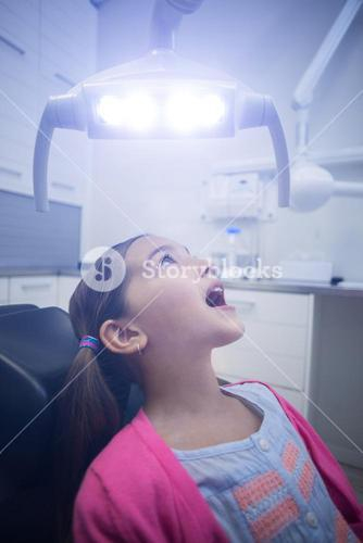 Young patient sitting on dentists chair with mouth open