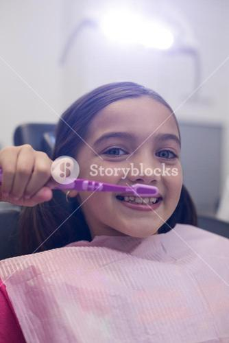 Young patient brushing her teeth