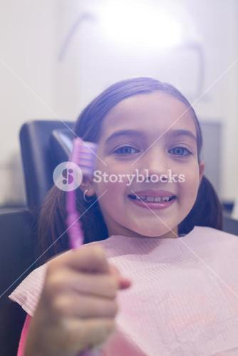 Young patient holding her toothbrush