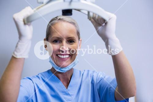 Smiling dental assistant adjusting light in clinic
