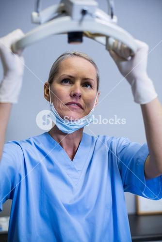 Dental assistant adjusting light