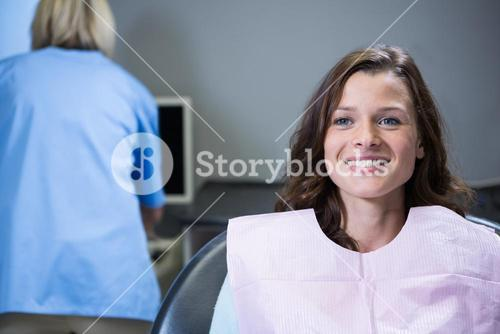 Smiling patient sitting on dentists chair